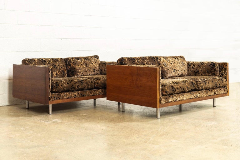 This pair of vintage Mid-Century Modern two-seat case loveseat sofas in the style of Milo Baughman and circa 1970 have incredible style. With a clean elegant profile, the loveseat couches feature two-seat cushions, two backrest cushions and two