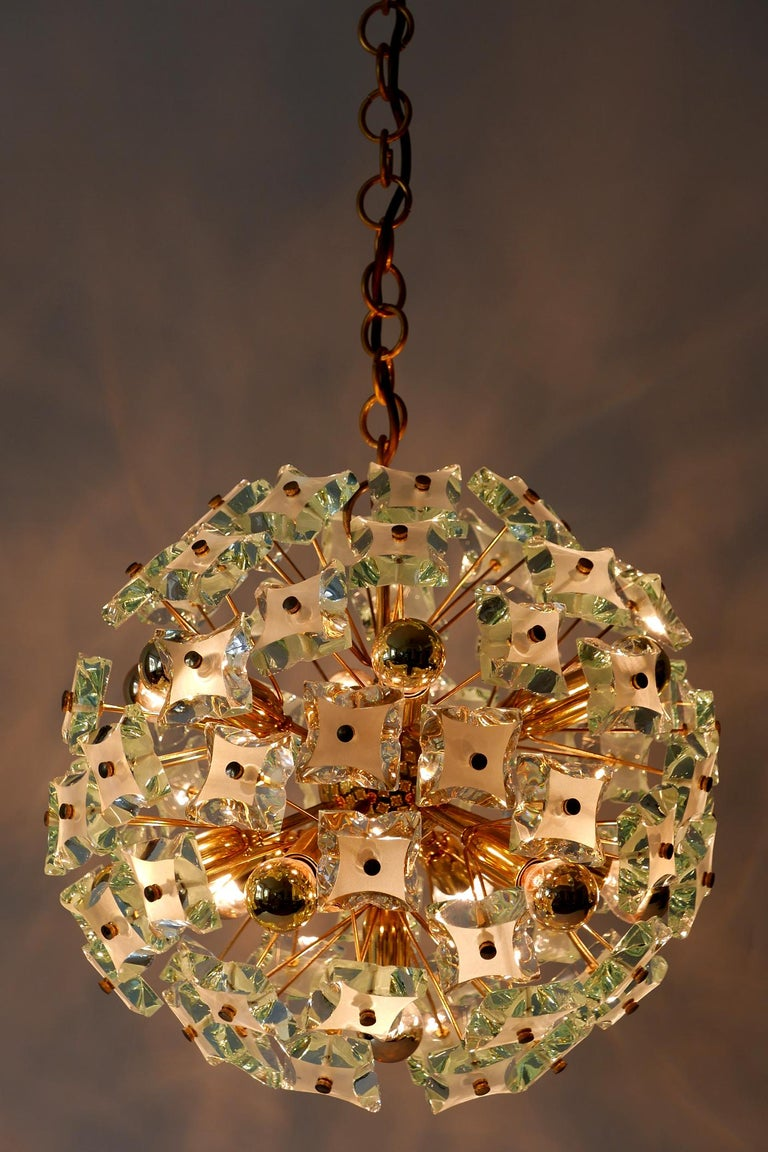 Amazing and highly decorative, elegant Mid-Century Modern Sputnik 13-flamed chandelier or pendant lamp 'Dandelion'. Manufactured probably by Fontana Arte in 1960s in Italy.  Executed in thick glass and brass, the chandelier / pendant lamp needs 13 x