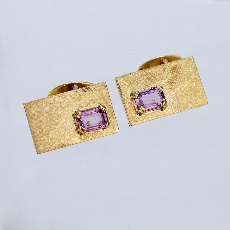 A fine pair of modernist 14K gold & amethyst cufflinks.  With textured rectangular gold faces prong set with rectangular amethyst gemstones to the corners.   The button backs are connected to the faces with chain links.  Unmarked for fineness.