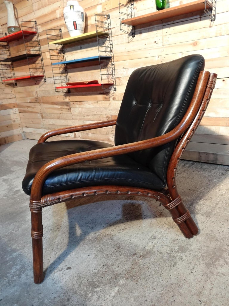 Mid-Century Modern 1960 colonial cane / bamboo designer sling-back black leather chair.  In very good vintage condition.  Measures: Seat height: 40cm, height: 80cm, depth: 75cm, width: 66cm.