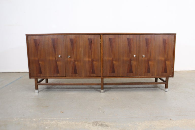 Offered is a vintage Mid-Century Modern walnut credenza with four parqueted doors. Includes inner shelving and three dovetailed drawers. One drawer has dividers with felt lining for silverware. It has been refinished and its pulls have been replaced
