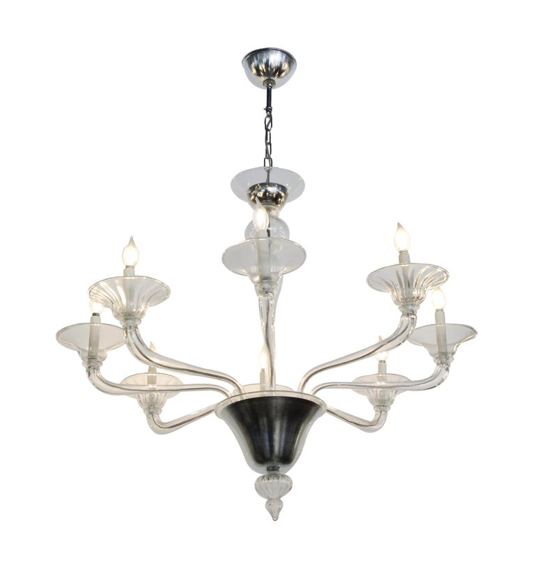 Mid-Century Modern style eight-arm chandelier made of glass and steel with a brushed finish. This can be seen at our 2420 Broadway location on the upper west side in Manhattan.