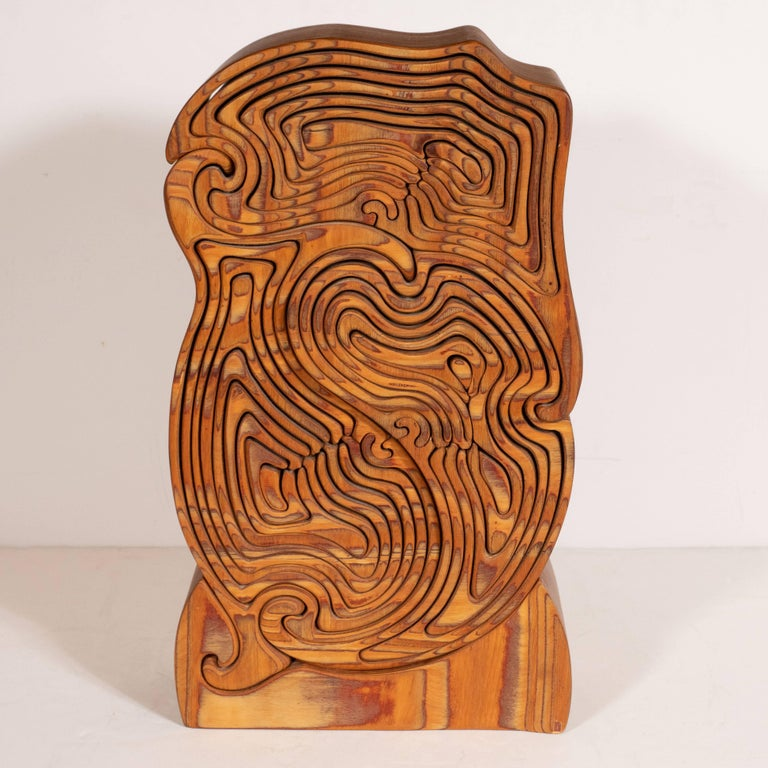 This kinetic and impeccably crafted olive wood sculpture was realized, by hand, in the United States, circa 1970. It offers a an abundance of intertwining curvilinear forms that fit together, like abstracted nesting dolls. The dimensional form