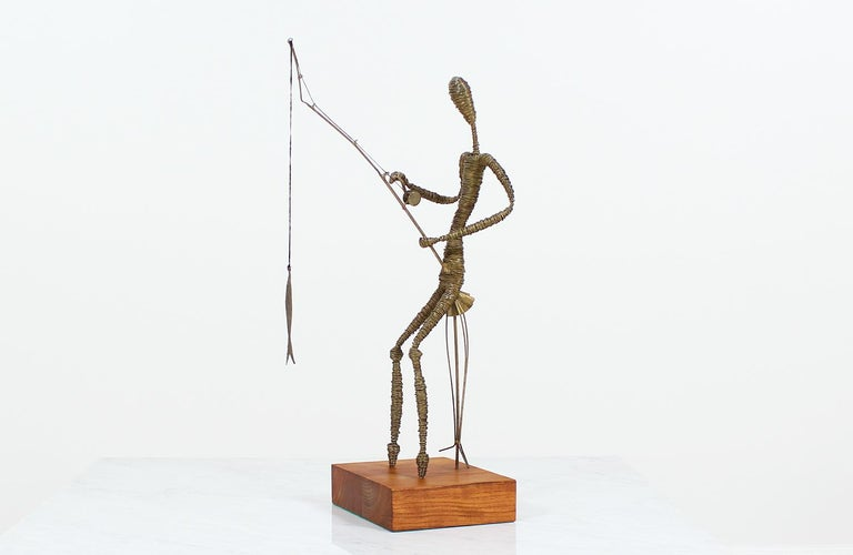 Mid-Century abstract sculpture made in the United States circa 1960's. This metal fisherman sculpture is mounted on a squared teak wood base and shows a beautiful patina on the metal from age. Brass wires are bound together to create an abstract