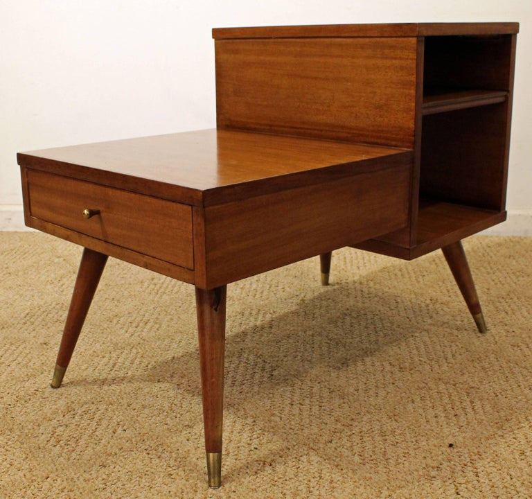 This table was made by American of Martinsville. It is a two-tiered walnut end table featuring one dovetailed drawer and shelving.