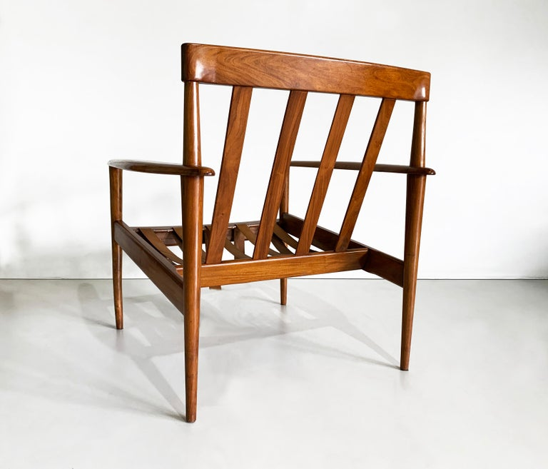 Grete Jalk design produced by Ambiente in the 1960's in Brazil. This armchair, often attributed to Rino Levi, was part of his interior design projects.  This armchair is made of solid caviuna wood with leather strap. It still have remaining the