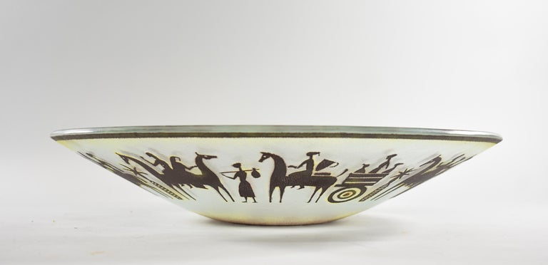 Beautiful art glass bowl with acid cut tribal scene in brown, red and yellow by Maurice Heaton. Heaton was born in Switzerland in 1900 and passed in New York at the age of 90. 15