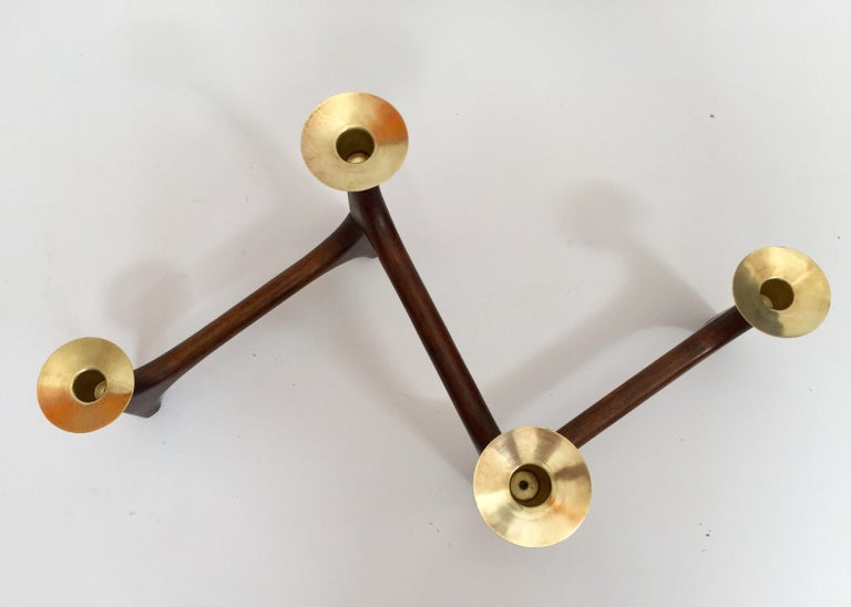Vintage 1960s modernist candle holder, teak and polished brass articulating candlestick. Mid-Century Modern handcrafted modern teak wood and brass candlestick centerpiece. This stained wooden candle holder features a folding frame with four brass