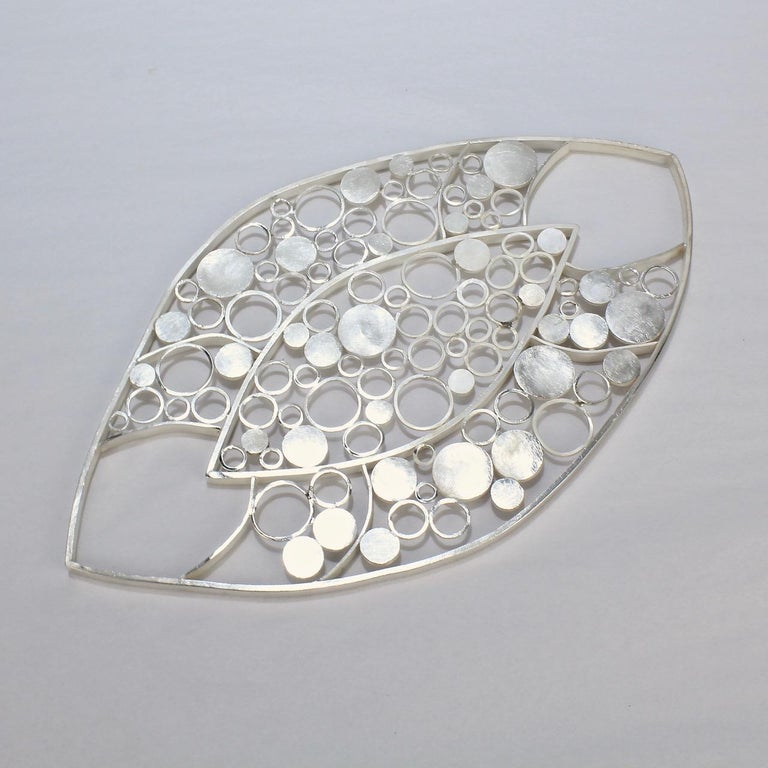 A whimsical, modernist sterling silver trivet.   With a hand soldered ring and dot pattern in an asymmetrical oval form and with a brushed finish.  Perfect for a wine bottle or serving bowl!  The reverse is stamped Sterling and with the artist's