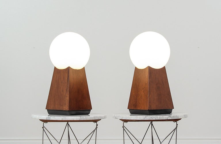 Pair of elegant table lamps designed and manufactured in the United States circa 1960s. These fantastic modern lamps feature a walnut wood body with an exquisite grain detail throughout adding texture and warmth to this rare design. The bases have