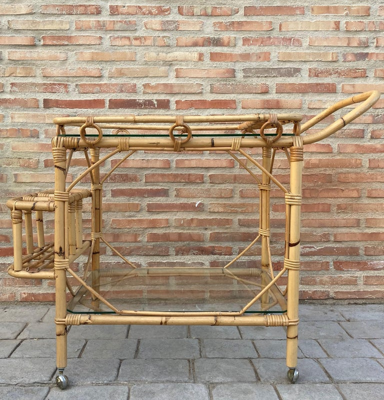Mid-Century Modern bamboo tea cart, Fabulous from the 1950s. Made in bamboo with two large wheels. Bottle rack on the back. In perfect condition. Perfect for a collected garden of potted plants, or extra kitchen storage.   Height to the low