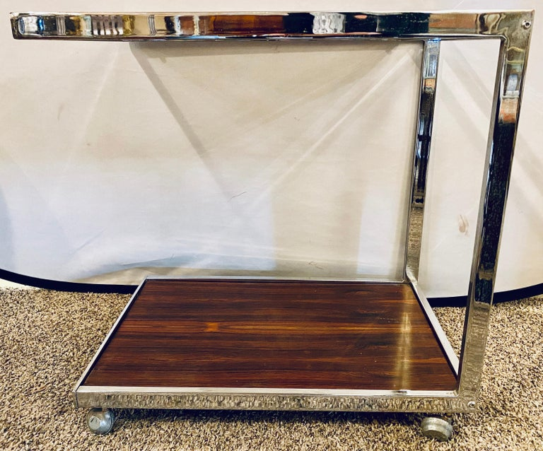 Mid-Century Modern bar or serving cart. Milo Baughman rosewood & chrome on casters. Having a smoked glass top and rosewood base this highly desirable and sweet bar or serving cart is not only love to view but highly functional. One of many pieces by