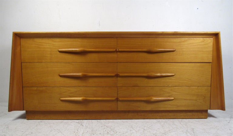 This stunning vintage modern bedroom set includes a dresser and two nightstands. The sculpted drawer pulls and angular design show quality construction. This set offers plenty of room for storage within its many drawers. Sleek case pieces with