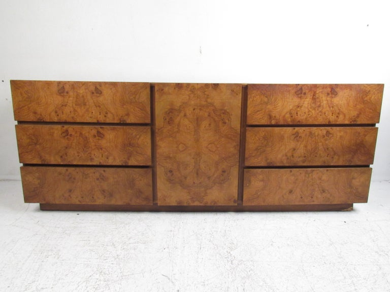 This stunning vintage modern bedroom set includes a low dresser, highboy dresser, two nightstands, two mirrors, and a unique headboard. A sleek design that offers plenty of room for storage within its many large drawers and compartments. A headboard