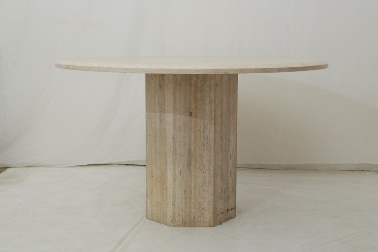 Elegant design for this round top table made of beige travertine. This table would easily fit 6 to 8 people and match with any interior due to its modern design with a polygonal base and a large round top (two separated parts).