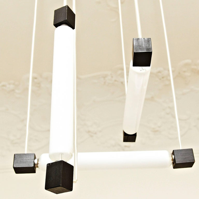 Hanging lamp, designed in the style of Rietveld, executed circa 1960 by unknown manufacturer. Painted wooden structure and plastic tube protecting the electricity cable, with three bulbs.  In good original condition, with minor wear consistent