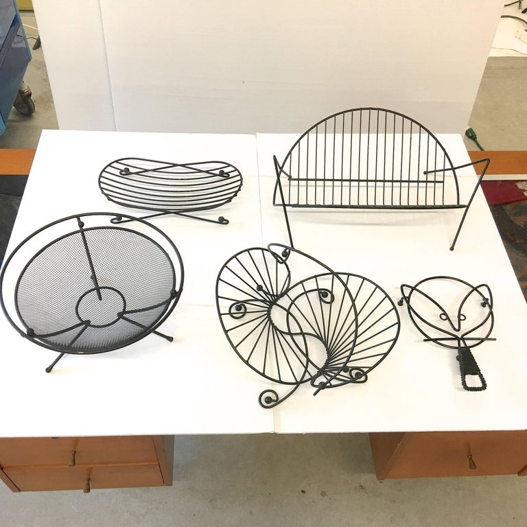 Grouping of Mid-Century Modern black wire organizers, catch-alls, racks and baskets. These evoke the highly appreciated post-war style of clean structural modern handcrafted decorative accessories by designers such as Tony Paul, Archie Kaplan, Sol