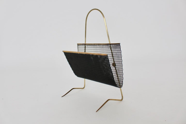 This presented vintage magazine rack in the style of Mathieu Mategot stands out through its extraordinary structure. Also the magazine basket of the magazine rack was made of black lacquered perforated metal and the feet were made of brass. Very