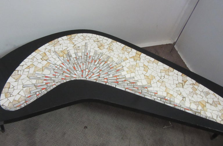 Mid-Century Modern boomerang coffee table with Mosaic tile top, made in the 1960s. The table was recently painted black and restored. tabletop has a mosaic tile top with red and yellow highlights and 3 legs. In great vintage condition with