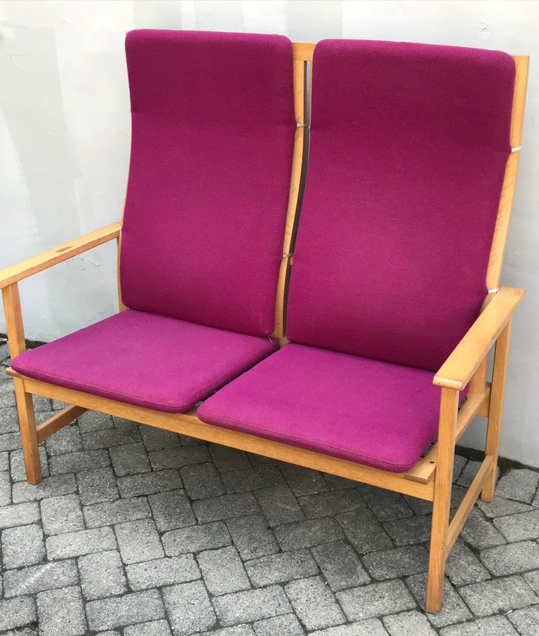 Mid century bentwood oak frame two-seat bench by Borge Mogensen for Fredericia Stolefabrik, Denmark. Maintains original vibrant raspberry colored cushions, wear appropriate, missing one strap down, one cigarette burn, no stains, many more years of