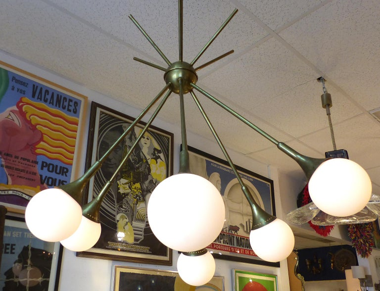 Mid-Century Modern Brass and Glass Sputnik Chandelier  Offered for sale is a Mid-Century Modern brass and glass globe six-light Sputnik style chandelier. The frosted white globes are irregularly positioned to create a light feeling with movement.