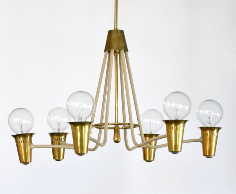 A lovely Mid-Century Modern chandelier of circular form with six painted metal arms held by a brass ring, ending in brass cups containing Edison base sockets. Suspended on a brass rod, which can be adapted to your height. Unmarked but most likely
