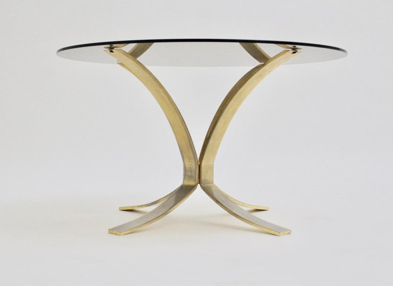 The coffee table by Roger Sprunger for Dunbar Furniture, USA, shows a brass-plated base with brass patina and also a smoked glass top. approx. measures: Diameter: 80 cm (glass diameter) Height 47 cm (including the glass top).