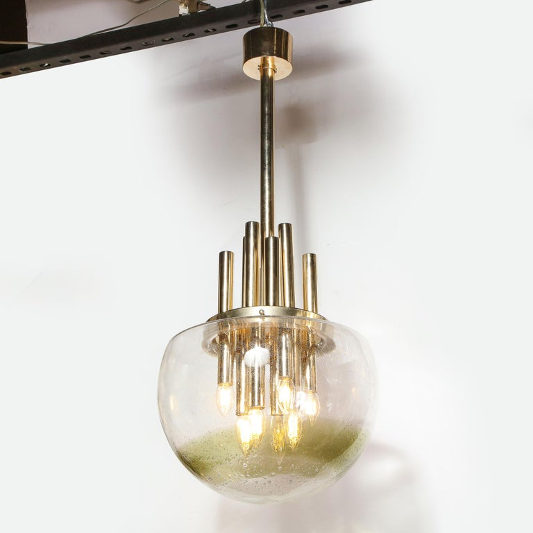 This sophisticated Mid-Century Modern chandelier was realized in Italy, circa 1970 by the esteemed atelier of Mazzega. The fixture offers eight cylindrical brass rods of staggered lengths that descend into a concave globular translucent hand blown