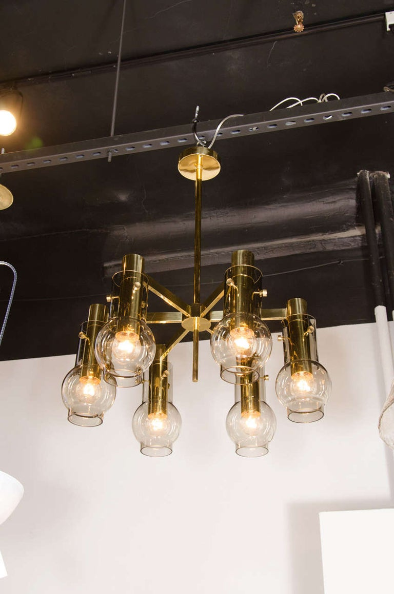 This refined Mid-Century Modernist chandelier was designed by the esteemed Hans Agne Jakobsson in Sweden, circa 1960. It features six rectangular arms emanating from a circular body, all in polished brass. A cylindrical rod of the same material