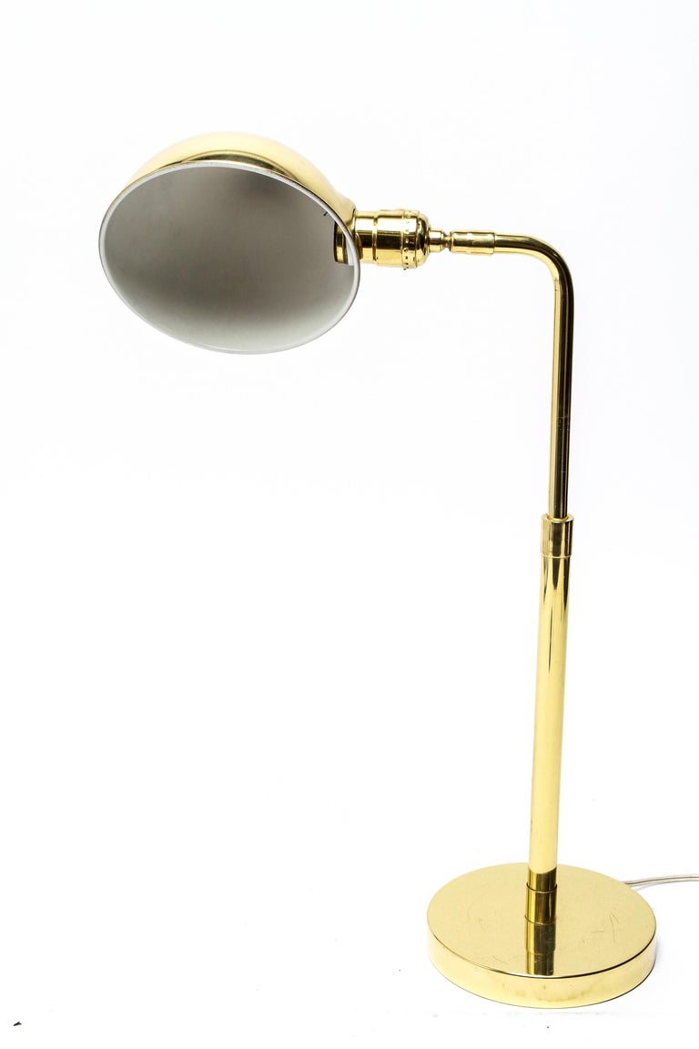 Mid-Century Modern polished brass table lamp or desk lamp with a dome demilune shade. The shade interior bears a partial label. The height of the lamp can extend. In great vintage condition with age-appropriate wear.