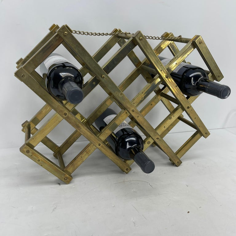Mid-Century Modern brass foldable wine rack with decorative chain along top. The rack holds 10 bottles of wine. The wine rack has an aged brass patina. Fully collapsible, this sturdy wine rack can easily be transported to any on the go party or