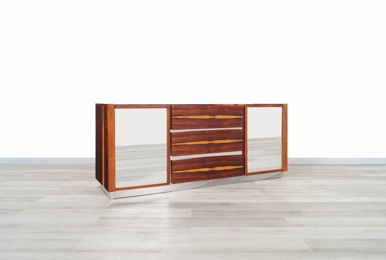 Mid-Century Modern rosewood credenza or dresser manufactured in the United States, circa 1960s. This credenza features a total of nine drawers. Three drawers are hidden behind each mirrored glass door. Plenty of storage space. The case consists of a