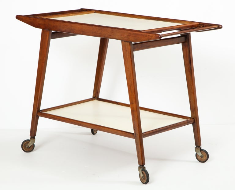 Mid-Century Modern Brazilian tea cart in Peroba Rosa hardwood with removable tray in white formica by OCA Manufacture.  This elegant wheeled tea-cart or bar-cart was produced in the 1950s by OCA Brazil Manufacture. It features two trays in white