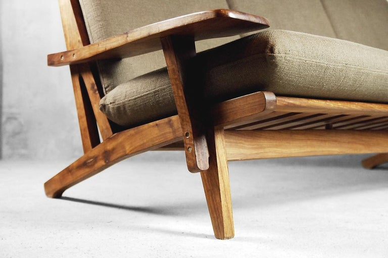 This beautiful piece of midcentury design was manufactured in Brazil during the 1960s. It is made of wonderful exotic wood with strong grain. The upholstery is made of high quality earth colored fabric, perfectly fitting with the natural color of