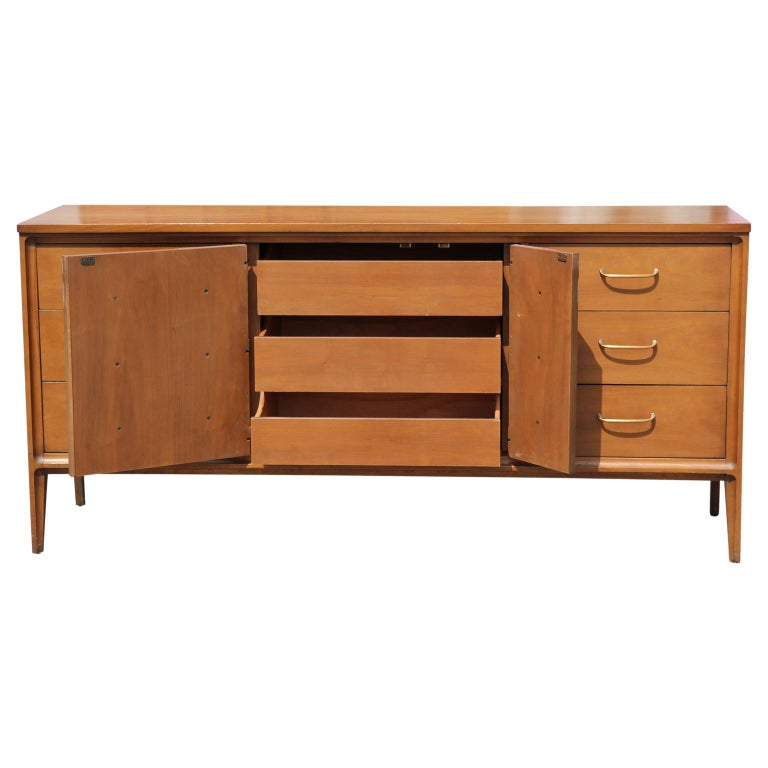 Sleek Mid-Century Modern design sideboard by Broyhill with 6 drawers and 3 more concealed drawers behind a swing out panel. The makers mark is on the inside of the top drawer. The sideboard is in great vintage condition.