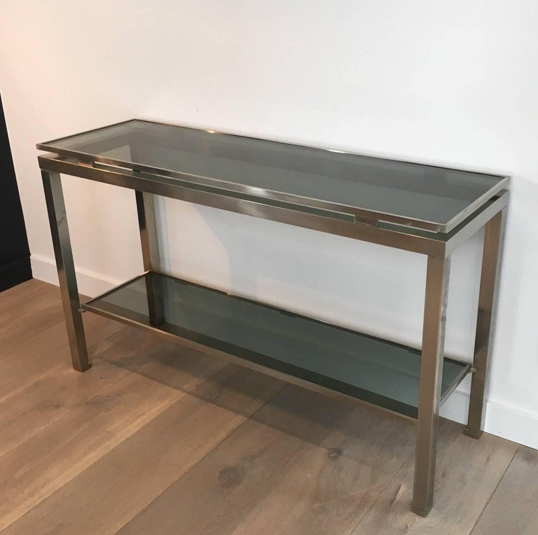 A Mid-Century Modern console made of brushed steel with blue/grey glass shelves. Designed by Guy Lefèvre for Maison Jansen, French, circa 1970s.   This console is currently in France, please allow 2 to 4 weeks delivery to New York. Shipping cost