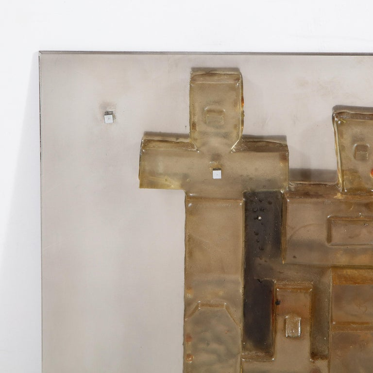 This refined Mid-Century Modern brutalist wall sculpture was realized in the United States, circa 1970. It features a patchwork mosaic of adjoined amber forms affixed to a brushed aluminum backplate. The amber shapes occupy an interesting liminal