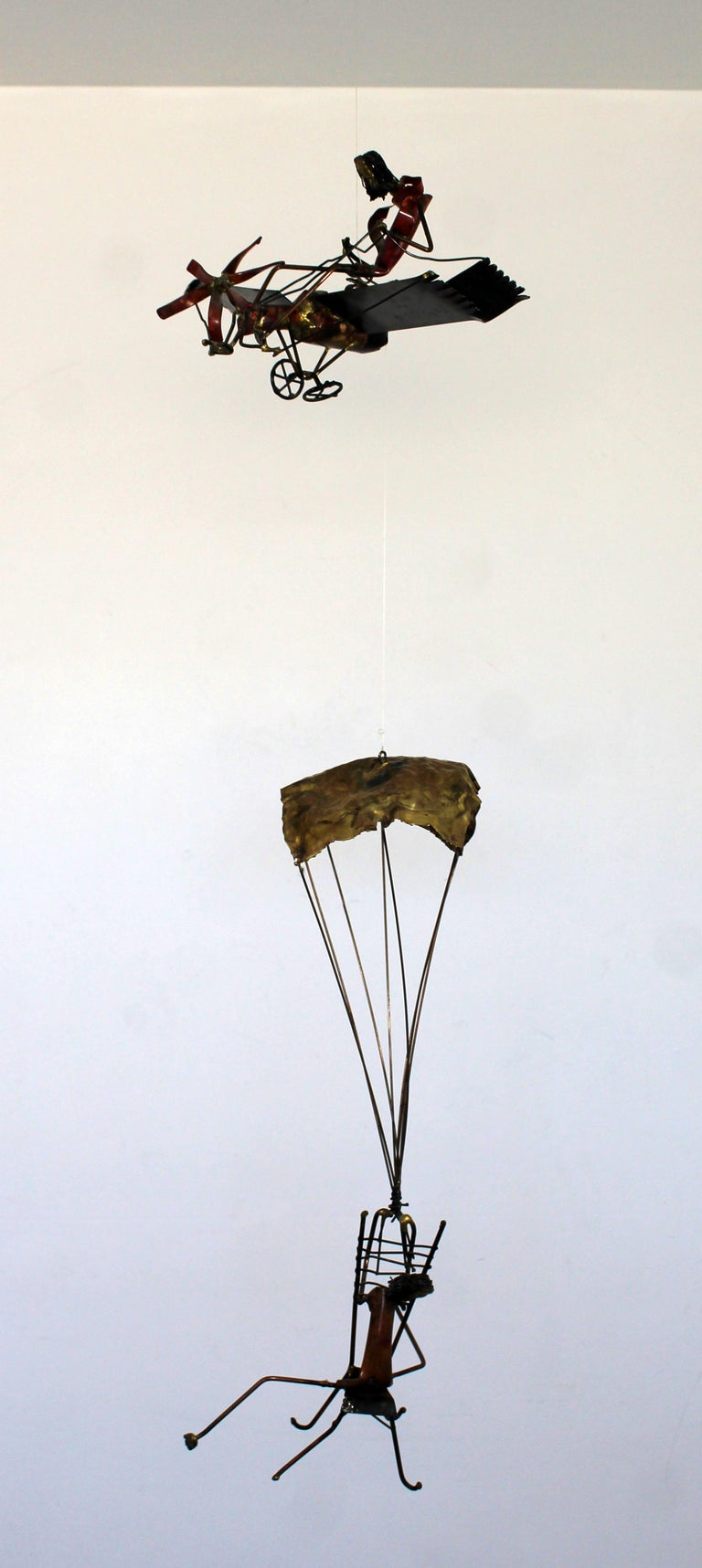 For your consideration is a whimsical, Brutalist brass wall sculpture of a man in a plane and a man hanging by a parachute beneath, in the style of Curtis Jere, circa 1970s. In excellent vintage condition. The dimensions are 12