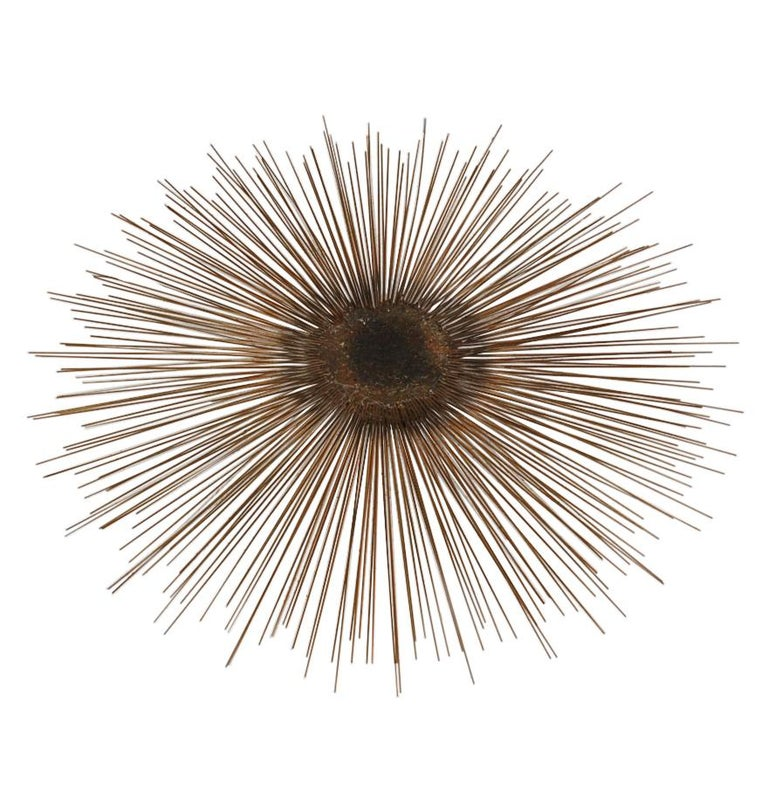 A striking sunburst wall sculpture from the 1960s Brutalist period. It features hand welded brass and steel construction. Unmarked.