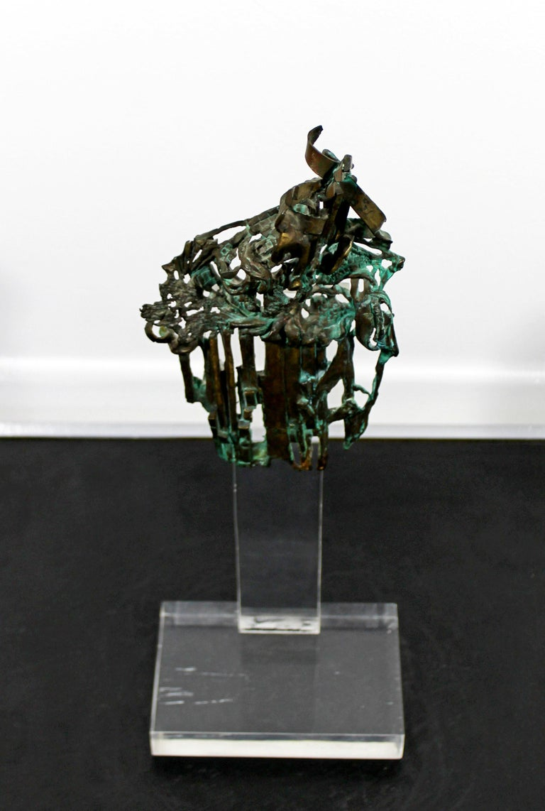 For your consideration is a brilliant, Brutalist, abstract, bronze table sculpture on a clear acrylic Lucite base, signed Glen Michaels, circa 1970s. In excellent condition. The dimensions are 6