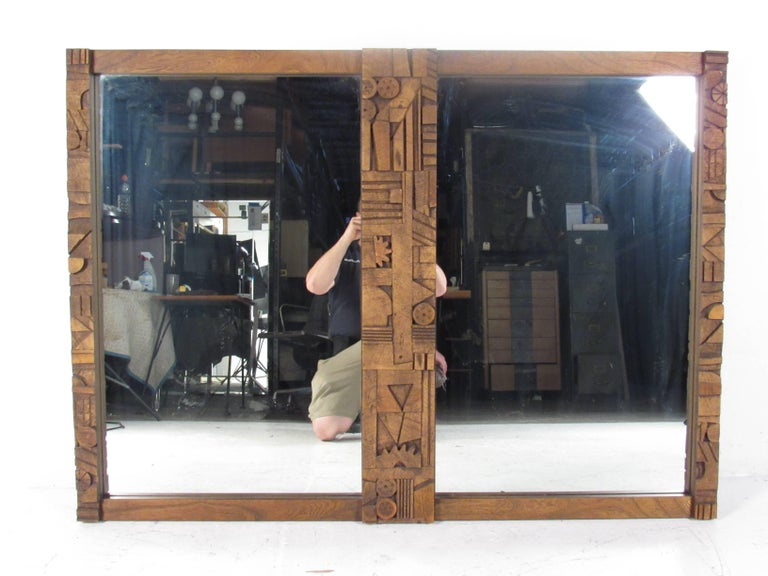 This impressive vintage modern mirror features a Brutalist design in the center. A wonderful and unique piece that can be used as a wall mirror or attached to the back of a credenza. Extremely thick walnut wood designed by Lane Furniture. Please