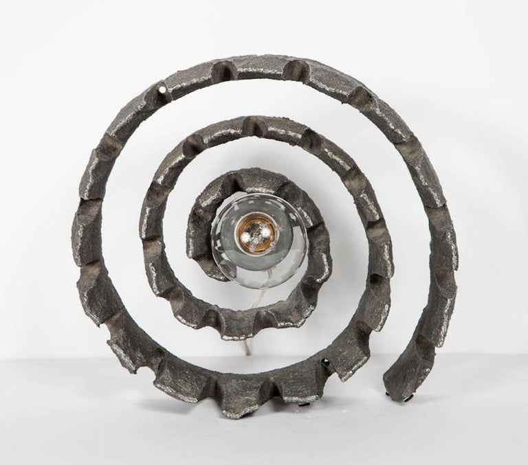 Mid-Century Modern table lamp and sculpture. Features hand forged spiral or wheel form. Brutalist design comprised of textured cast iron metal. Single Light bulb and socket easily removable, converts the piece from functional light fixture to art