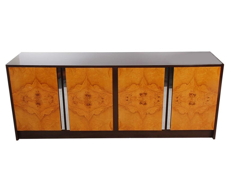 A handsome looking 4-door credenza in the manner of Milo Baughman or Pierre Cardin, circa 1970s. It features a glossy chocolate brown case with beautiful contrasting olive burl doors.
