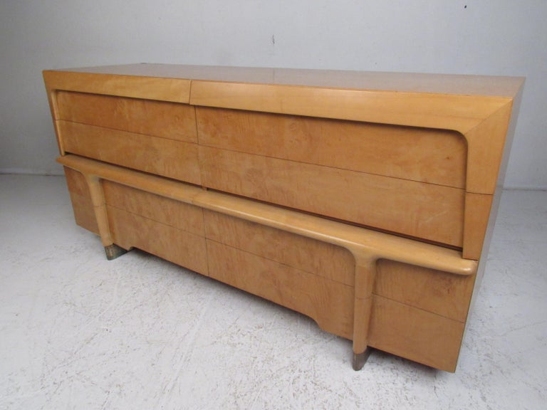 This impressive vintage modern bedroom set includes a highboy dresser, low dresser, and two nightstands. A unique design that boasts a sculpted front, sled legs, and drawers with dovetailed joints. This handsome bedroom set offers ample room for