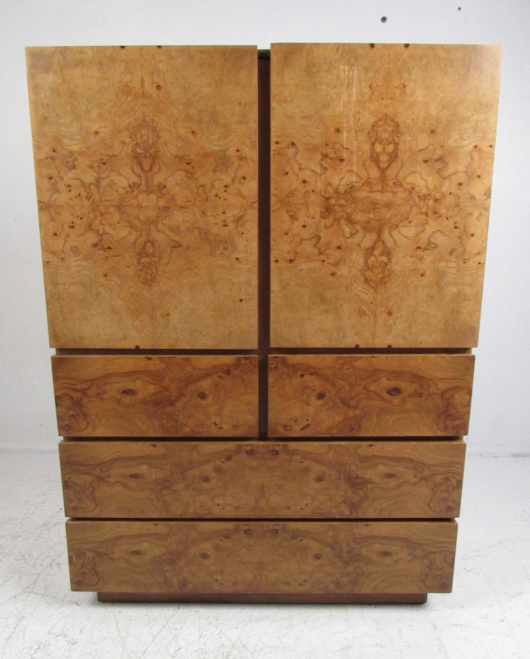 This impressive vintage modern armoire boasts a spacious interior and hefty drawers. A straight line design with a rich golden burl wood finish and lacquer makes this piece an eye catching addition in any modern interior. By Lane Furniture. Please