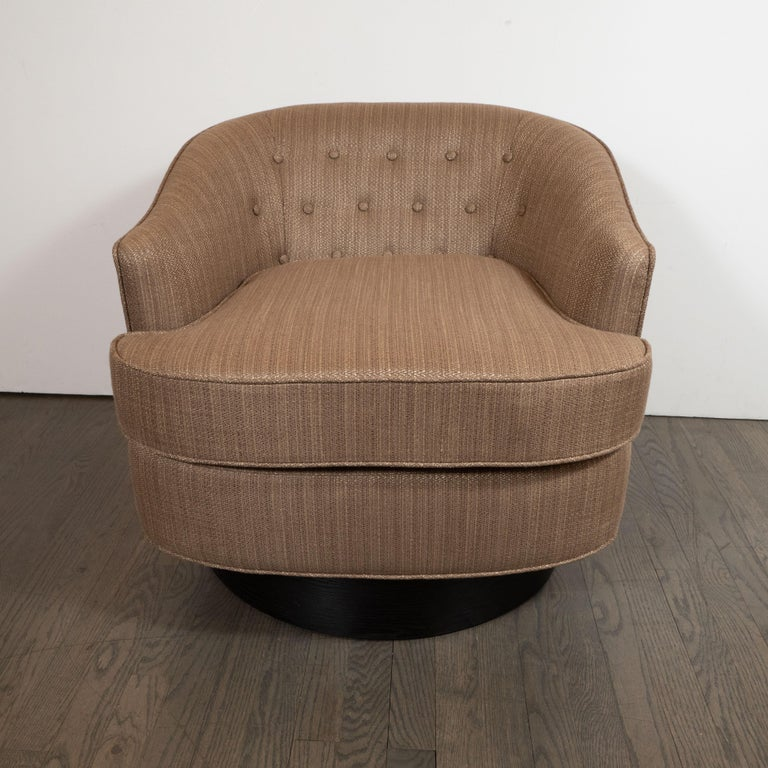 This refined Mid-Century Modern chair was realized in the United States circa 1960. It features a curved button back and gently sloped arms, and an exceedingly comfortable seat filled with foam wrapped down. The piece sits on a circular ebonized