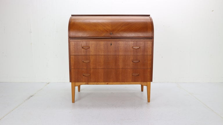 This iconic midcentury Swedish modern teak cylinder rolltop secretary- desk- cabinet is made in 1970s Sweeden by Egon Ostergaard designer and manufactured by Markaryds Mobelindustri manufacture. The Classic Scandinavian Modern design has clean