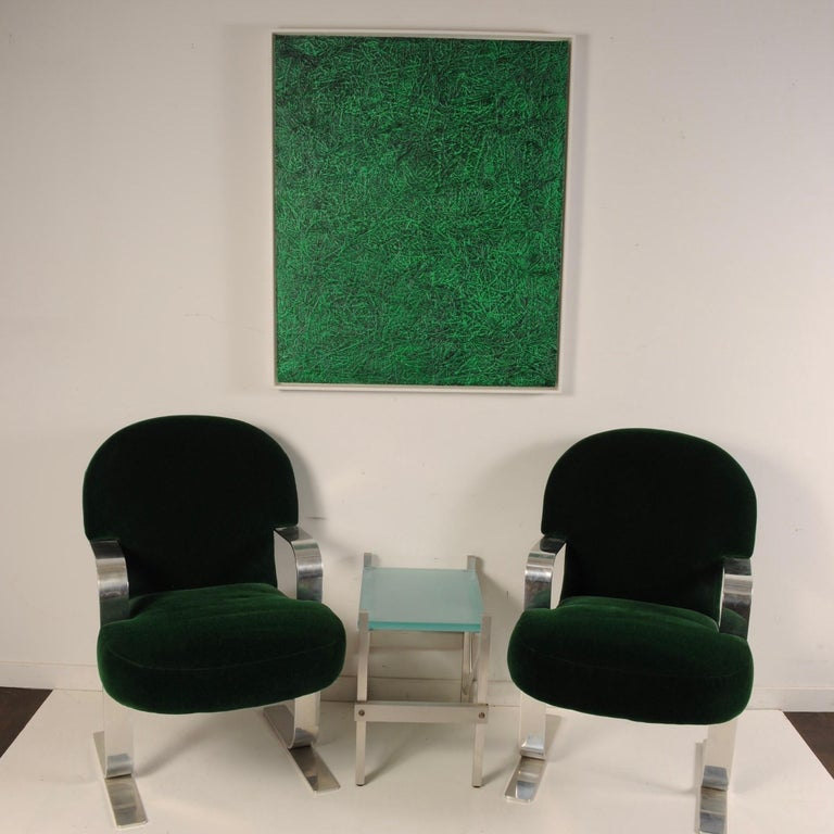 Clean pair of cantilevered armchairs in hunter green mohair with heavy, polished steel arms and legs. A nice blend of Art Deco with a modern Brueton-like polished frame. The design of the legs is rather unique to this chair. Haven't seen this design