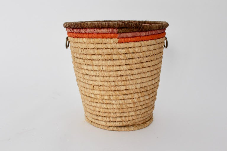 This presented vintage paper basket made of straw with two brass handles was designed and executed by Carl Auböck, Vienna, circa 1950.