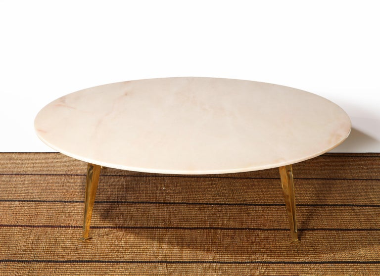 A true Italian Mid-Century Modern gem. This coffee table consists of a large polished cream with blush colored Carrara marble top with delicately carved and pointed solid brass legs which is reminiscent and likely attributed to the work of Italian